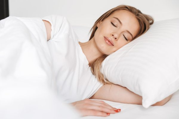 Cute pretty woman sleeping in bed indoors at home
